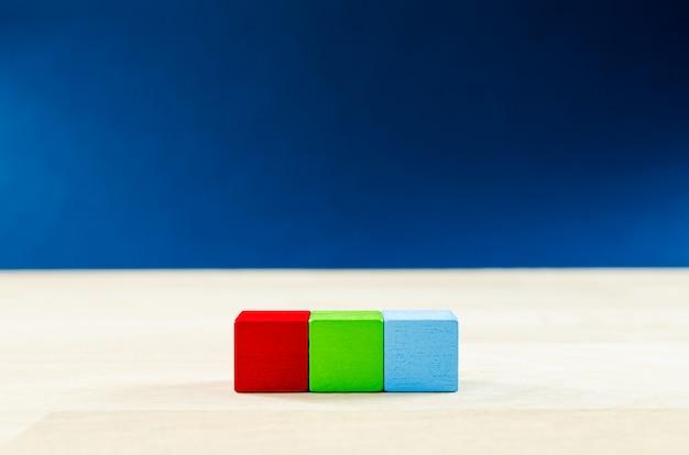 Drei leere holzklötze, rot, grün und blau, in einer reihe.