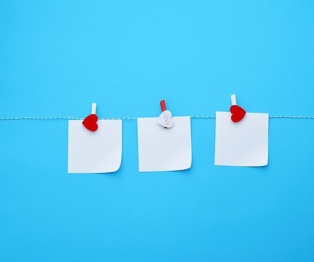 Drei leere quadratische weiße papierblätter hängen an dekorativen wäscheklammern