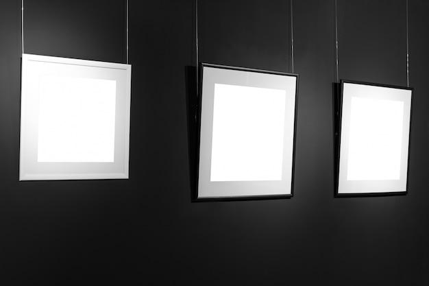 Drei leere rahmen an der schwarzen wand. leere raumplakate oder kunstrahmen warten darauf, gefüllt zu werden. quadratische schwarzweiss-rahmen