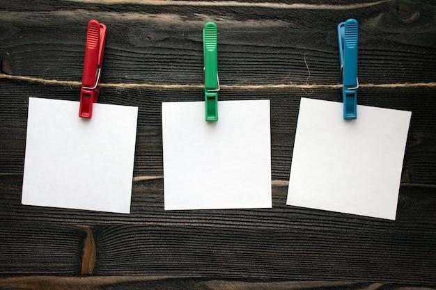 Drei leere schablonenquadratbroschüren auf seil auf wäscheklammern