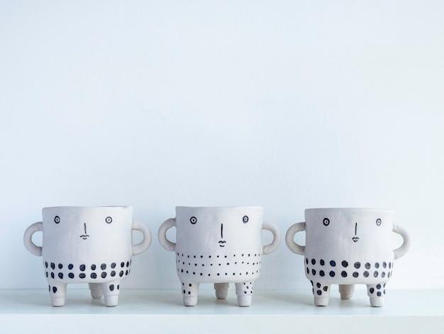 Drei leere, süße gesichtstöpfe aus keramik auf weißem holzregal isoliert auf weißer wand mit kopierraum. kleine moderne diy-zementpflanzer trendige dekoration.
