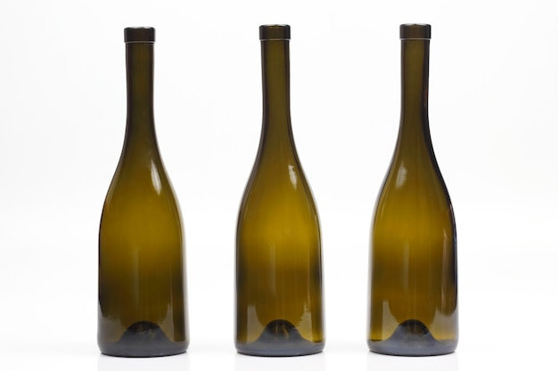 Drei leere weinflaschen auf weißem hintergrund
