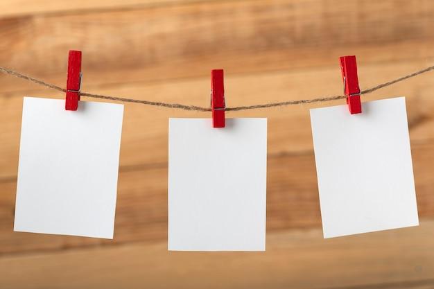 Drei leere weiße notizkarten, die mit wäscheklammern hängen