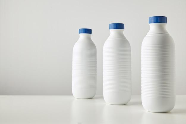 Drei leere weiße plastikflaschen mit blauen kappen in der reihe isoliert auf dem tisch