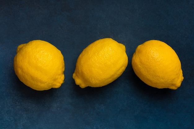 Drei leuchtend gelbe zitrusfrüchte auf blauem hintergrund draufsicht