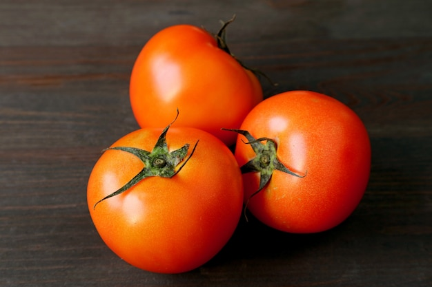 Drei leuchtend rote tomaten auf dunkelbraunem holztisch