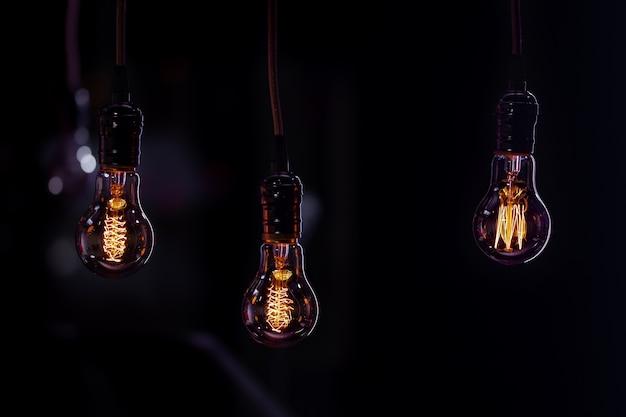 Drei leuchtende lampen hängen im dunkeln am buch. dekor- und atmosphärenkonzept.