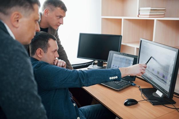 Drei leute. polygraph-prüfer arbeiten im büro mit der ausrüstung seines lügendetektors