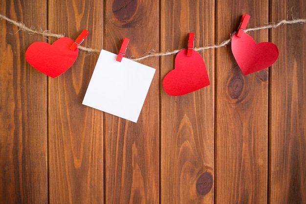 Drei liebesherzen, die am hölzernen beschaffenheitshintergrund, valentinstagkartenkonzept hängen