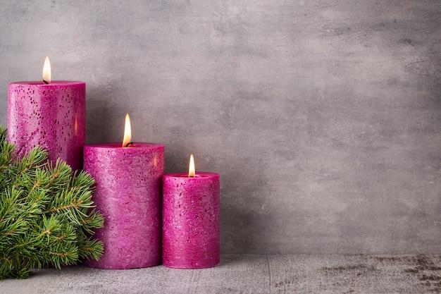 Drei lila kerzen auf grauem hintergrund, weihnachtsdekoration. adventsstimmung.