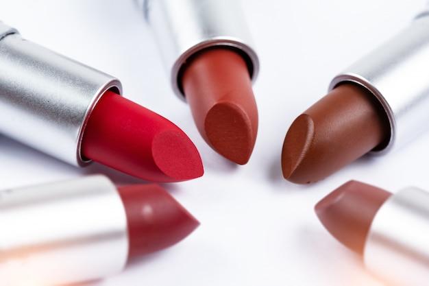 Drei lippenstifte auf weißem hintergrund, zeigen pigment und textur der farbe