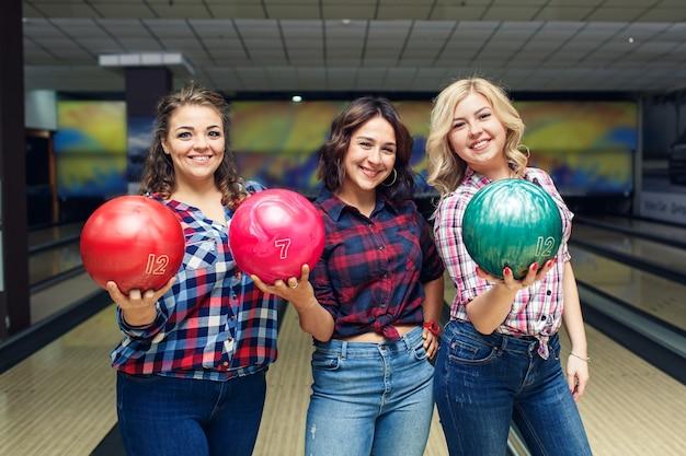 Drei lustige attraktive freundinnen halten bowlingkugeln und schauen dich an.