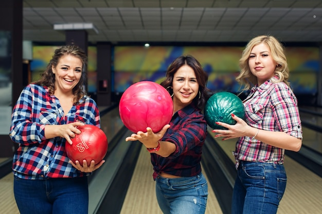 Drei lustige attraktive freundinnen halten bowlingkugeln