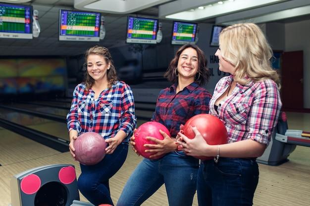 Drei lustige attraktive freundinnen nehmen bowlingkugeln.