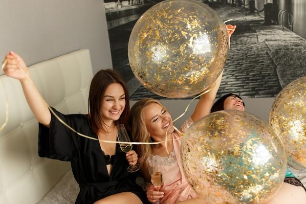 Drei lustige mädchen, die spaß zu hause im schlafzimmer haben