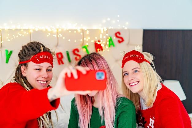 Drei lustige mädchen in weihnachtspullovern machen selfies. foto in hoher qualität