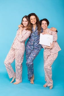 Drei mädchen, die bunte pyjamas tragen, die spaß auf blau haben