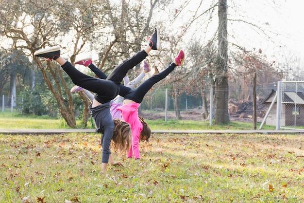 Drei mädchen, die den handstand trainiert im park tun