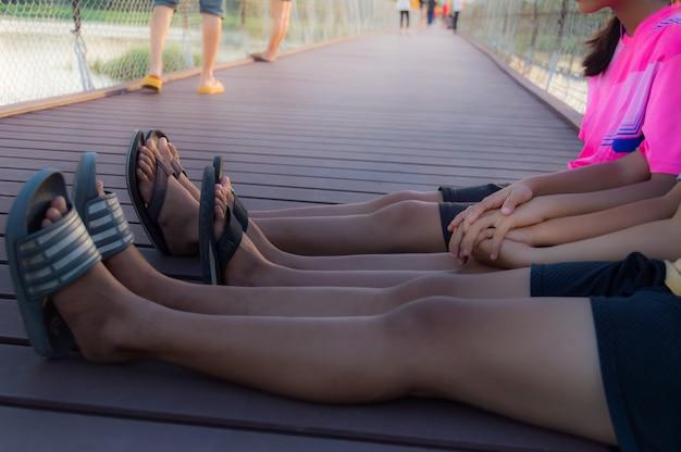 Drei mädchen, die hände, sitzen auf einer holzbrücke halten.