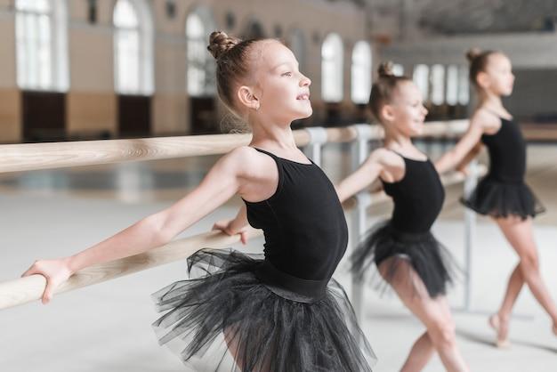 Drei mädchen, die mit hilfe von barre im tanzstudio aufwerfen