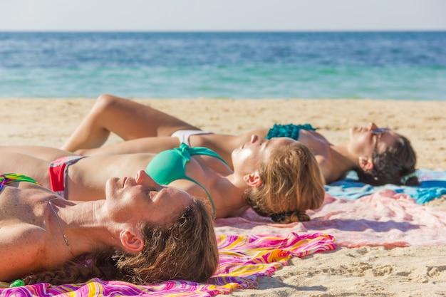 Drei mädchen, die sich am strand in der insel koh phangan, thailand sonnen. freundinnen, die auf bunten sarongs im sand am meer liegen. reiseziel, urlaubskonzept