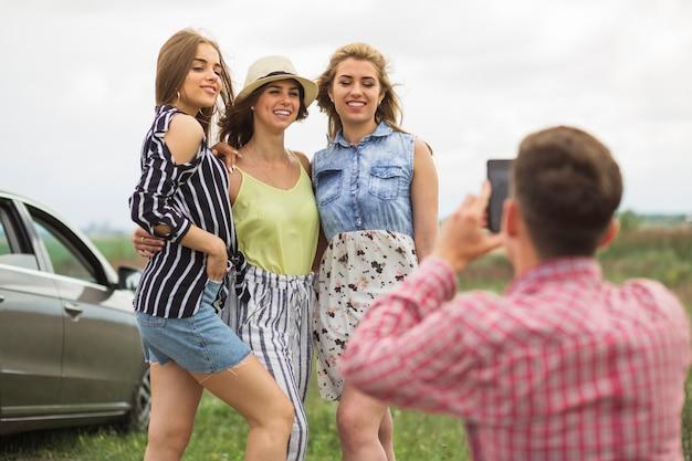 Drei mädchen, die vor dem mann macht foto aufwerfen