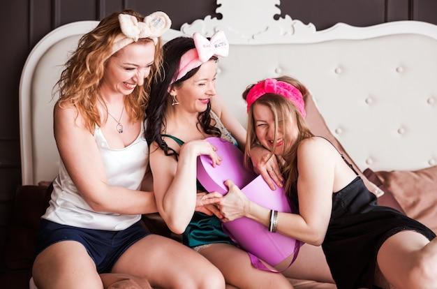 Drei mädchen einer freundin warfen eine pyjama-party auf ein plüschbett. mädchen können keine geschenkbox teilen.