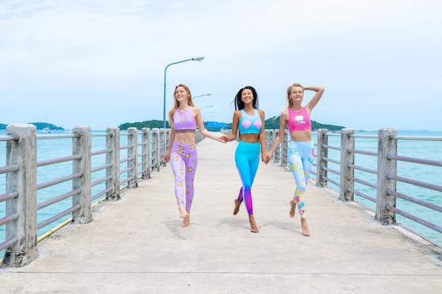 Drei mädchen entspannen sich auf dem pier und werfen in der modernen eignungskleidung auf.