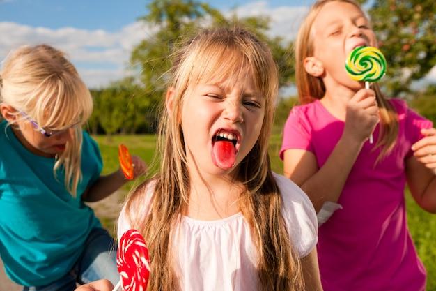 Drei mädchen essen lollypops