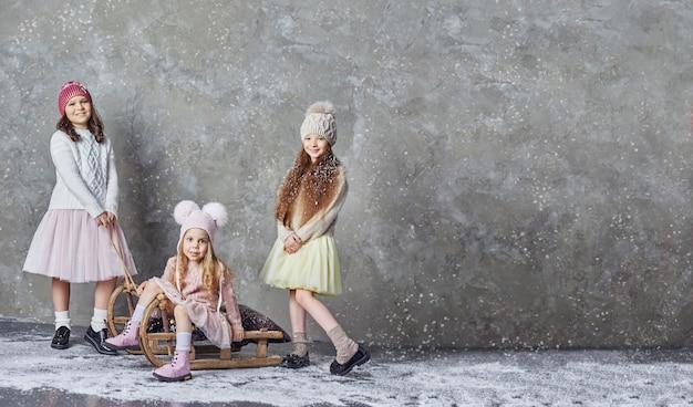 Drei mädchen haben spaß beim spielen und rodeln, schöne kinder genießen die ankunft des winters. russland, swerdlowsk, 18. november 2018