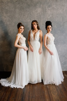 Drei mädchen im studio in eleganten weißen kleidern. hochzeitsfoto, schöne bräute im studio.