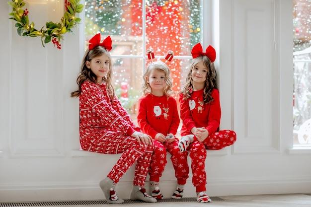 Drei mädchen im weihnachtspyjama sitzen nahe am fenster mit schnee draußen.