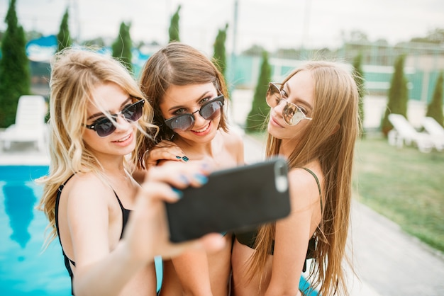 Drei mädchen in badeanzügen und sonnenbrillen machen selfie