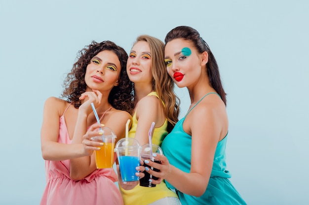 Drei mädchen mit künstlerischem make-up halten plastikgläser