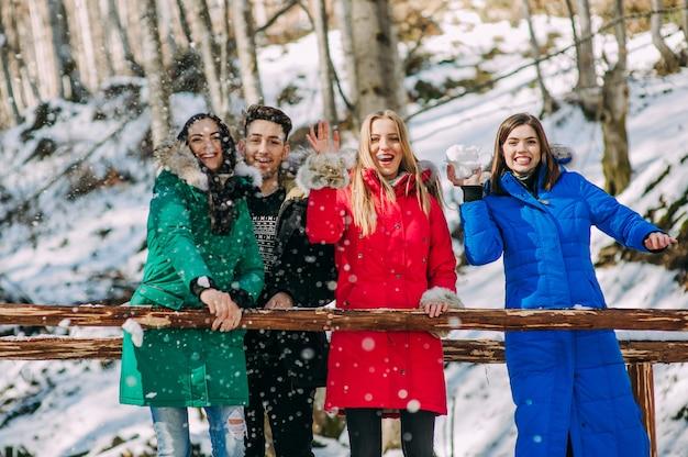 Drei mädchen und ein junge im winterwald