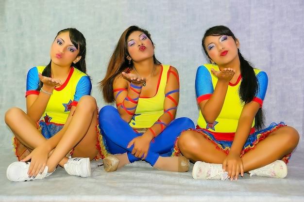 Drei mädchen verkleidet als cheerleader fröhlich mit bunten kostümen