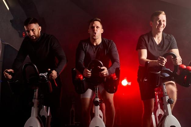 Drei männer, die in einem fahrradsimulator im fitnessstudio beschäftigt waren und auf einem stationären fahrrad trainierten, isoliert in einem dunklen, neonbeleuchteten, rauchigen raum