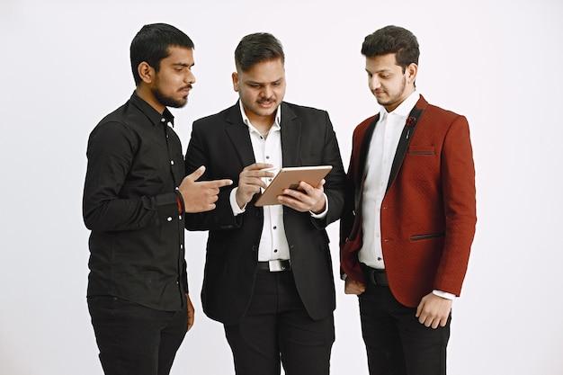Drei männer diskutieren über ideen. weiße wand. indische nationalität.