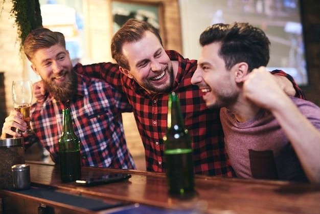 Drei männer genießen die gemeinsame zeit in der kneipe