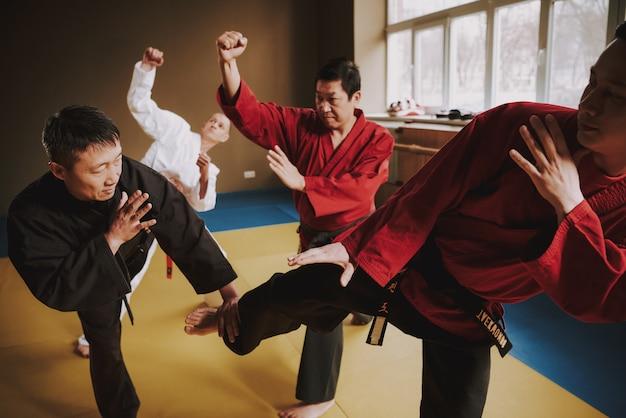 Drei männer greifen gemeinsam den meister an und er verteidigt