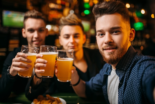 Drei männer hoben ihre gläser mit bier für den spielsieg in einer sportbar, glückliche fußballfans
