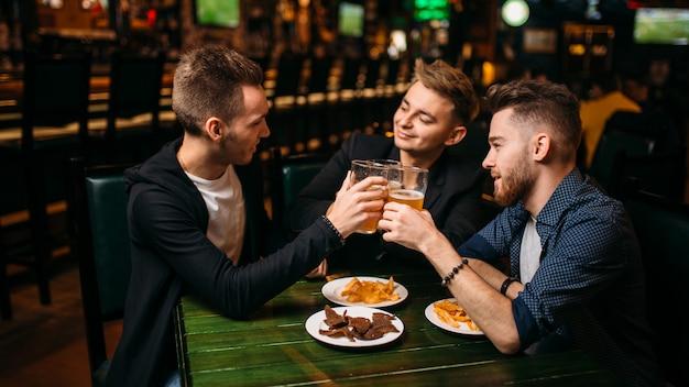 Drei männer hoben ihre gläser mit bier, um in einer sportkneipe den sieg zu erringen