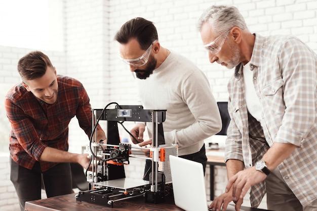 Drei männer richten einen selbstgebauten 3d-drucker ein.