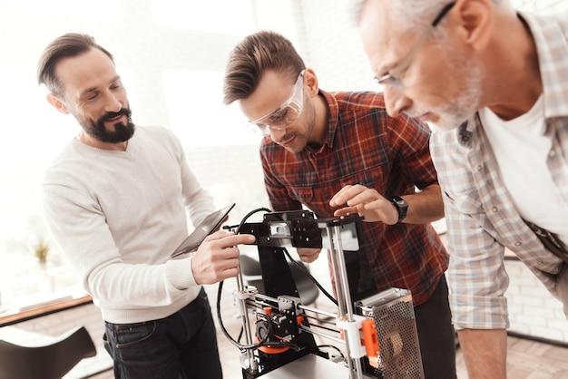 Drei männer richteten einen selbstgebauten 3d-drucker ein, um das formular auszudrucken.