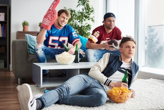 Drei männer schauen sich das spiel mit bier und snacks an
