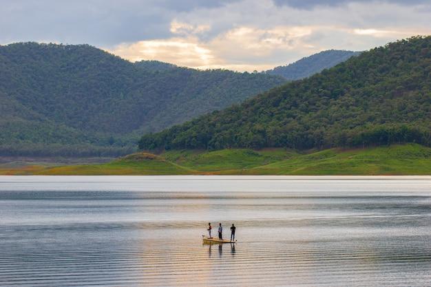 Drei männer stehen auf dem boot und fischen mitten im damm zwischen bergen.