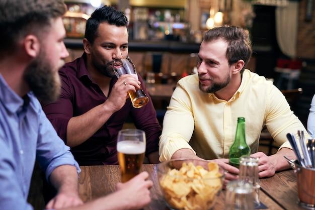 Drei männer verbringen zeit zusammen in der kneipe