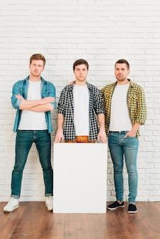 Drei männliche freunde mit dem weißen leeren plakat, das kamera betrachtet