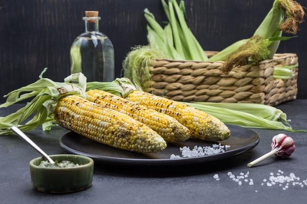 Drei maiskolben vom grill mit blättern und salz auf schwarzem teller. soße in schüssel. roher mais im weidenkorb. schwarzer hintergrund. ansicht von oben