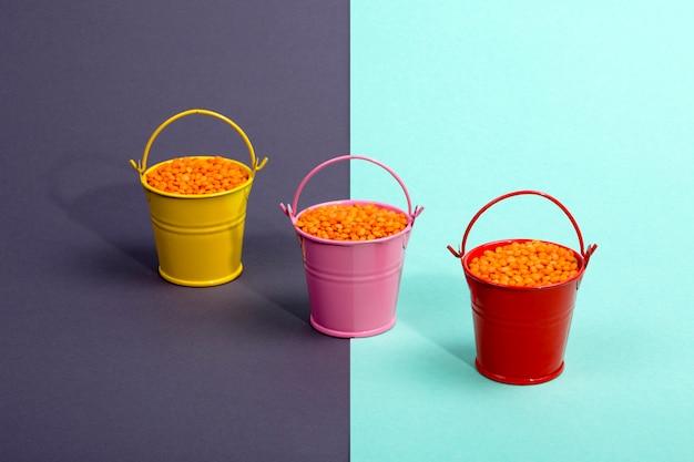 Drei mehrfarbige eimer mit orangefarbenen linsenbohnen